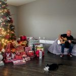 keith strumming guitar next to Christmas tree and cat.